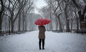 A woman stands with an umbrella during snowfall at Central Park in New York, US.