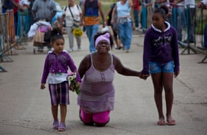 Maria Carbo, walks on her knees helped by her daughters as a self-imposed penance during her pilgrimage to the shrine in El Rincon, near Santiago de las Vegas, Cuba. Every year, tens of thousands of Cubans flock to the shrine to pay homage on the feast of Saint Lazarus, seeking favors from the religious icon, fused with Catholic and Afro-Cuban figures. He is known on the island as the 'miraculous saint'.