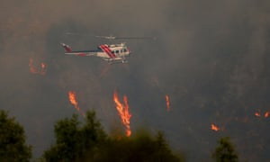 A helicopter flies over flames near Pfeiffer Ridge in Big Sur, California, US.  The wildfire fuelled by draught conditions has burned over 550 acres of land in the Los Padres National Forest.