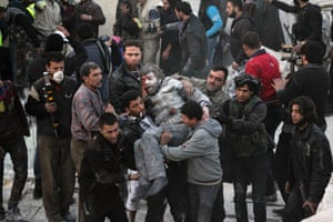 Residents carry an injured man who survived shelling after an air strike in Takeek Al-Bab area of Aleppo, Syria.