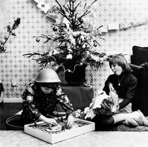 Children unwrap their Christmas presents. Amongst this young boy's Christmas presents is a 'Daleks' game relating to the popular television series, Dr Who.