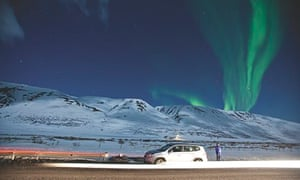 A car passses in front of a mountain behind which you can see the northern lights