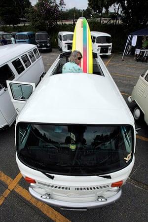 Volkswagen campers: A man arranges his surfboard inside his Volkswagen