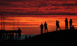 People gather to watch the sunset sky from a sand berm next to the Venice Beach pier, California, US