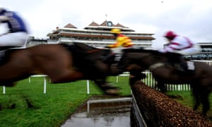 Runners clear the water jump at Newbury racecourse, UK, today.