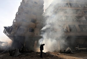 Goran Tomasevic: A building burns after a Syrian Air force air strike in the Ain Tarma neigh