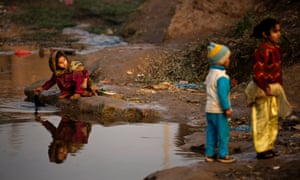 A girl displaced from a Pakistani tribal area of Bajur due to fighting between militants and security forces washes linens at a polluted stream in Islamabad's slum, Pakistan.
