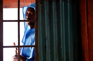 Goran Tomasevic: A man prays outside a church in the Kibera slum in Nairobi, during a prayer