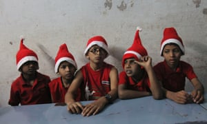 Indian children wearing festive hats wait to perform during Christmas celebrations at the Devnar School for the Blind in Hyderabad, India,.