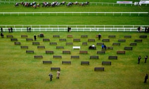 Racegoers look on as the runners pass the grandstands at Newbury racecourse, UK