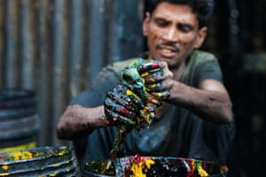 A man cleans paint from buckets in the slum area of Mumbai, India.