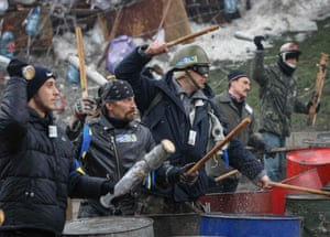 Pro-EU demonstrators bang on empty oil barrels at a barricade in Independence Square in Kiev, Ukraine.