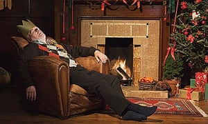 Man sleeping by fireplace in Christmas hat