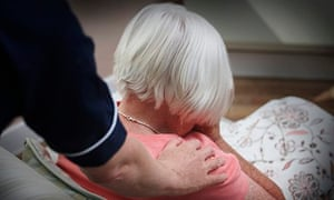 Carer supporting an elderly woman at home