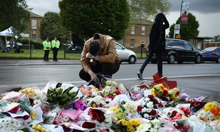 A man contemplates at a scene where flowers lay outside Woolwich Barracks