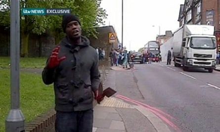 Video grab taken from ITV News of Michael Adebolajo with bloody hands holding a weapon at the scene