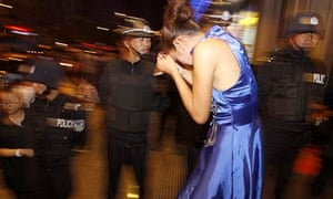 A woman suspected of prostitution is detained by police during a raid in Kunming, China