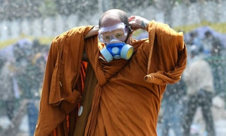 A Thai Buddhist monk puts on a gas mask as riot police use water cannon and tear gas in Bangkok