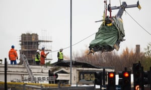 The wreckage of the police helicopter that crashed into the Clutha Vaults bar and pub is removed in one piece in Glasgow, Scotland.