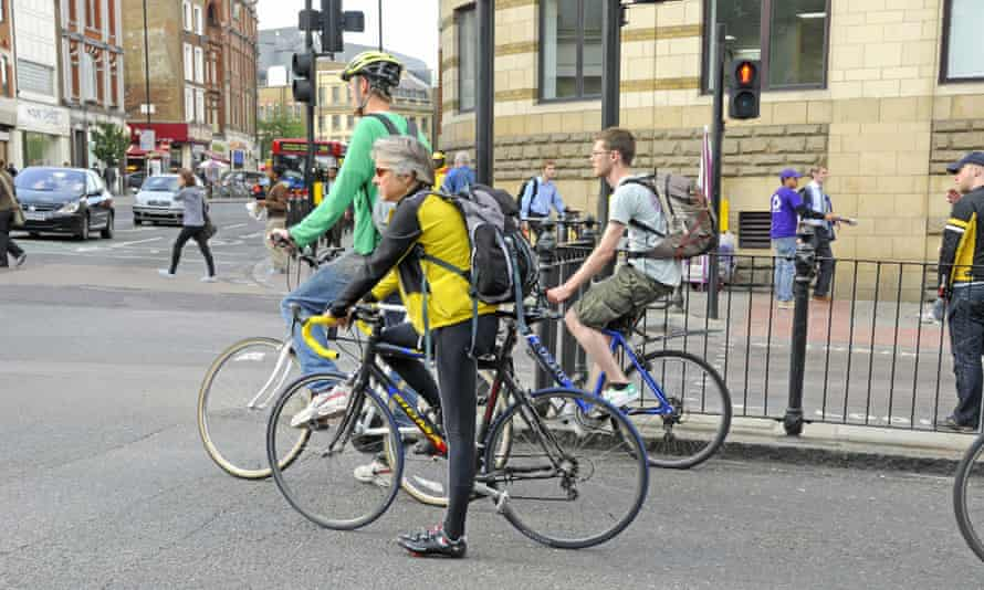 Cyclists held up at lights Angel Islington London England UK.