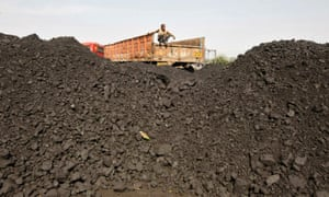 A worker sits on a truck as he waits for the loading of coal at a railway coal yard on the outskirts of the western Indian city of Ahmedabad.