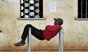 A man rests between two bars at a stadium in Mali's capital Bamako
