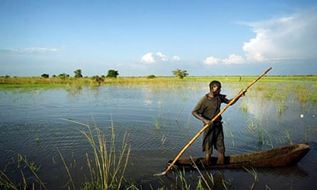A man paddles a canoe across a submerged rice field flooded by heavy rains in Soroti, Uganda