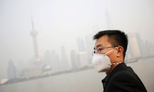 A tourist wearing a protective mask looks at buildings at the Bund under heavy haze in Shanghai