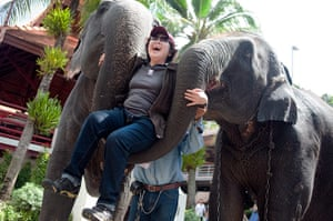 Chinese tourists: A woman is lifted by two elephants