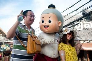 Chinese tourists: Chinese tourists pose with a mascot