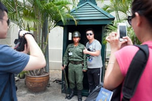 Chinese tourists: Tourists take turns posing with a guard by the exit to the Grand Palace