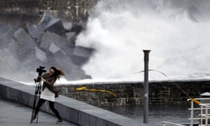 A woman appears to have some diffuculties to keep her balance while setting up a camera on a tripod to take images of the storm-battered sea at the Zurriola beach in San Sebastian, the Basque Country, northern Spain.