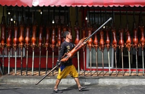 Top ten: Manila, Philippines: A worker carries roasted pig outside a store