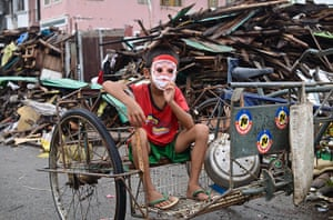 Top ten: Tacloban, Philippines: A boy with a Santa Claus mask sits on a pedicab amon