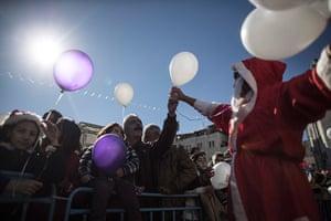 Top ten: Bethlehem, West Bank: A Palestinian man dressed as Santa Claus hands out ba