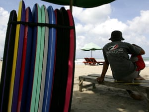 A surf board lender waits for customers at Kuta beach.