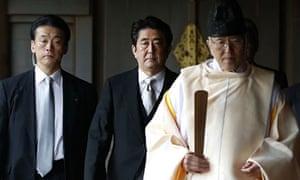 Shinzo Abe, centre, follows a Shinto priest as he visits the Yasukuni shrine for war dead.