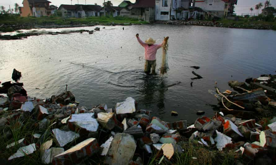 A man fishes with a net in the flooded area which was once a residential neighborhood of Banda Aceh, Indonesia.