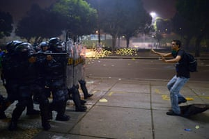 20 Photos: A protestor is shot by rubber bullets by anti-riot police officers in Rio