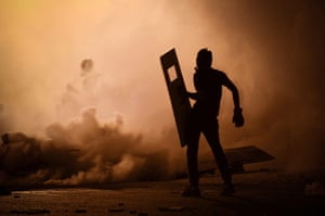20 Photos: A Bahraini protestor stands amidst teargas fired by riot police in Diraz