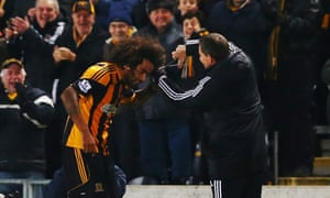 Hull City fans look on as Tom Huddlestone gets attention to his hair after scoring against Fulham