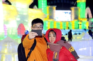 A young couple take selfies in front of ice sculptures at the Harbin ice and snow festival.