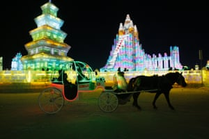 Tourists on a horse carriage pass by the large-scale ice sculptures at the 15th Harbin Ice and Snow World in Harbin, Heilongjiang province