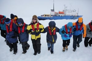 Passengers and scientists stomp an area of ice next to the Akademik Shokalskiy for a makeshift helicopter landing pad in readiness for evacuation from the trapped ship in Antarctica