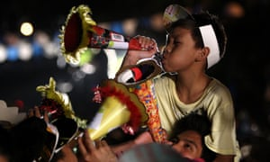 A Filipino boy blows his party blower.