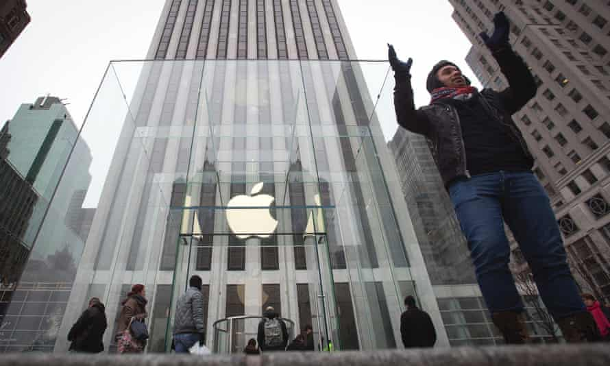 A man poses for a photo in front of the Apple store on 5th Avenue in New York.