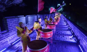 People dressed in traditional costumes play drums during a performance to celebrate the new year at the Great wall in Beijing.