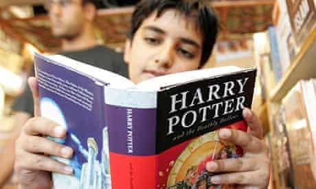 A boy reads a copy of Harry Potter