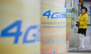 A customer looks at 4G advertisements in Yaiyuan, Shanxi province, China. The government has awarded 4G licences to carriers including China Mobile - which could soon sell iPhones.
