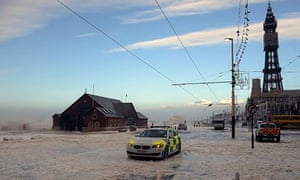A police car patrols the Blackpool seafront covered in foam and spray from the stormy weather